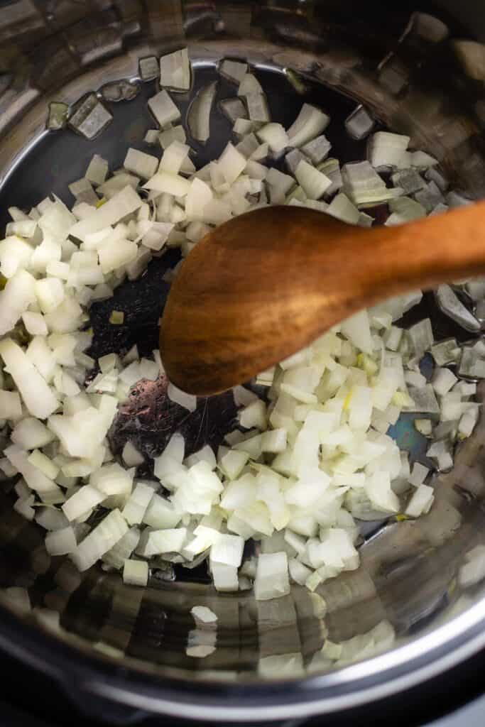 wooden spoon stirring onions