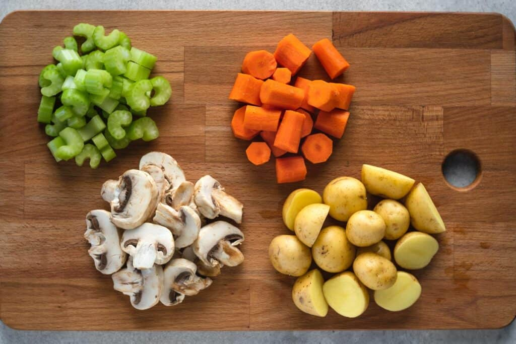 cutting board with chopped up celery, carrots, mushrooms, potatoes