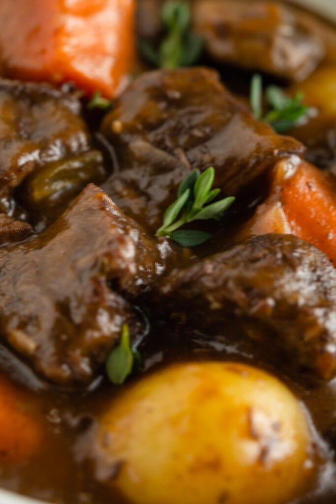 A close up of chunks of beef, carrots, potato and thyme leaves