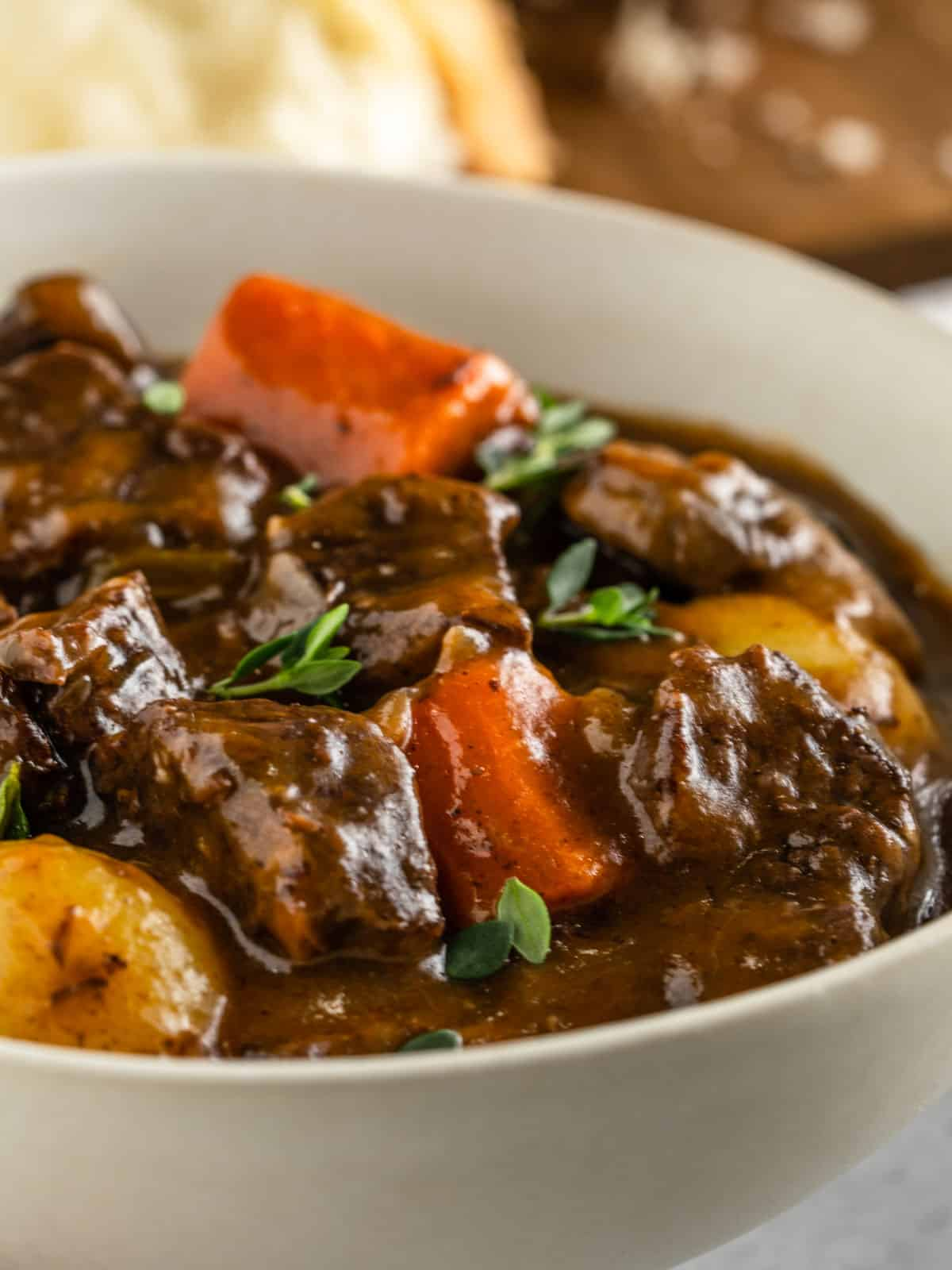 A white bowl of beef stew with beef, carrots, potatoes and garnished with fresh thyme leaves