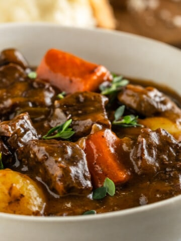 Bowl of beef stew with chunks of beef, carrots, and potatoes. Garnished with fresh thyme leaves
