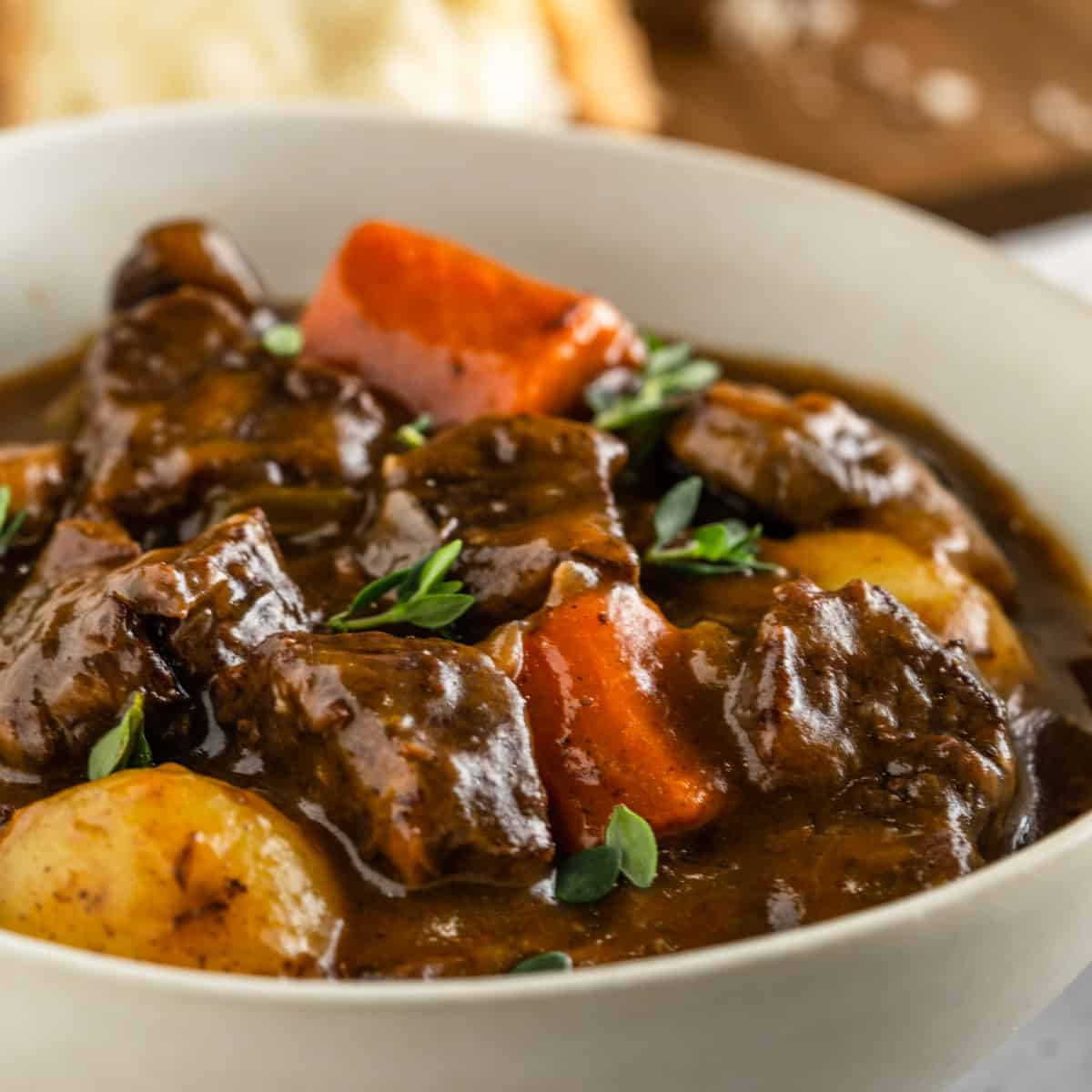 A bowl of beef stew with beef, carrots, potatoes and garnished with thyme