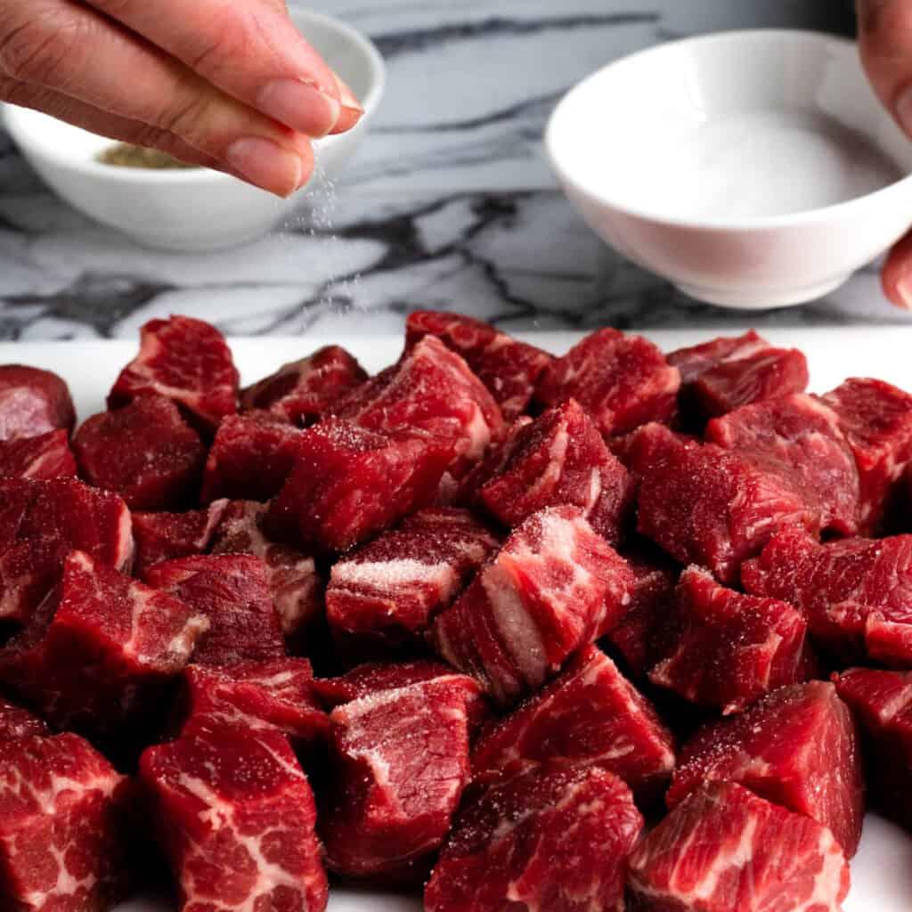 Hands sprinkling salt onto beef chunks