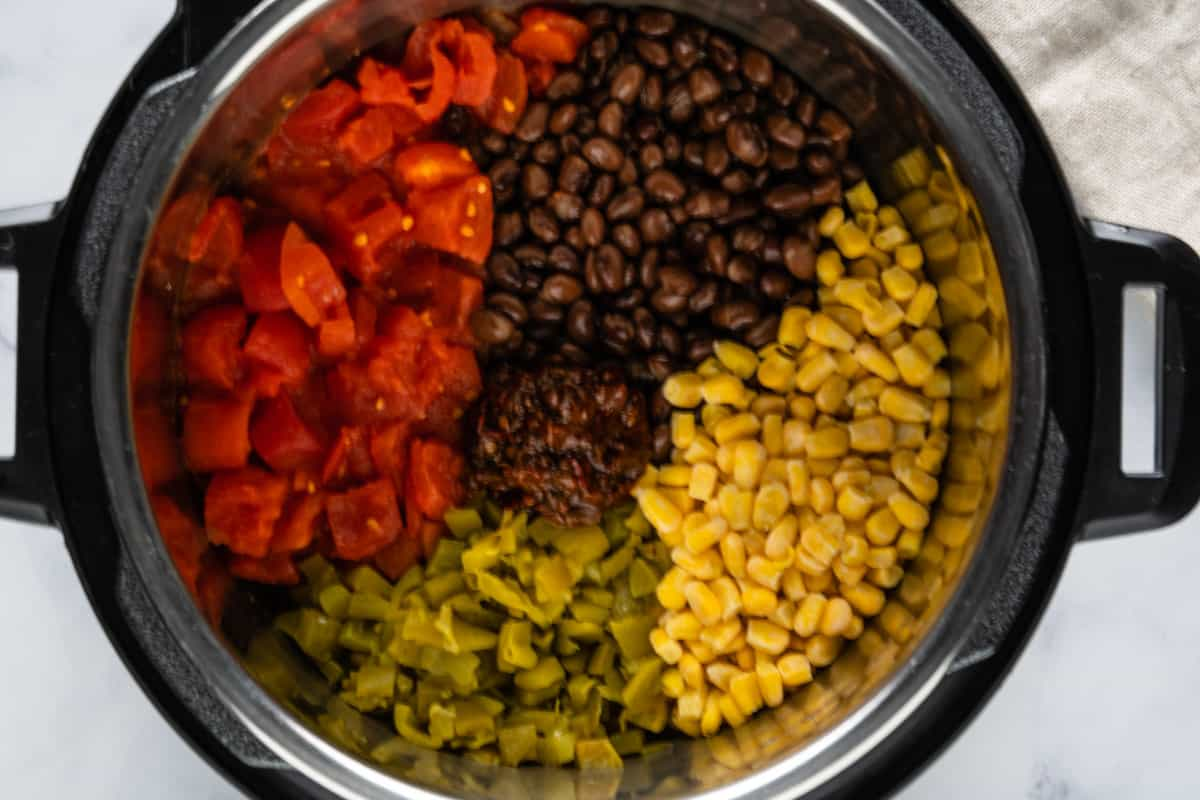 Ingredients in an Instant Pot: diced tomatoes, black beans, corn, diced green chilies and chipotle in adobo paste.