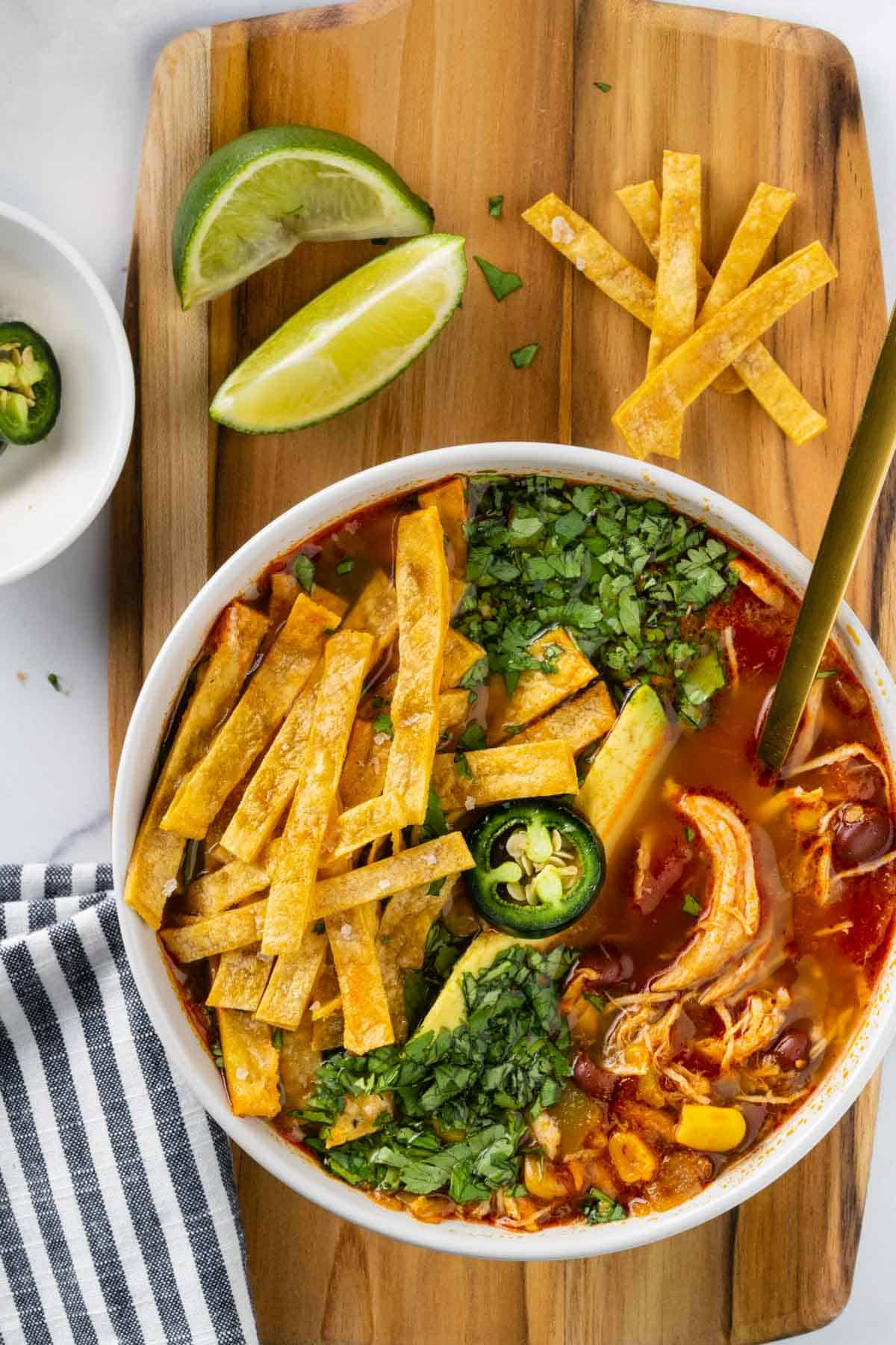 Bowl with chunks of chicken, beans, corn topped with tortilla chips, avocado, jalapeno and cilantro. Bowl is on a cutting board surrounded by sliced jalapeno peppers, lime wedges and tortilla chips.