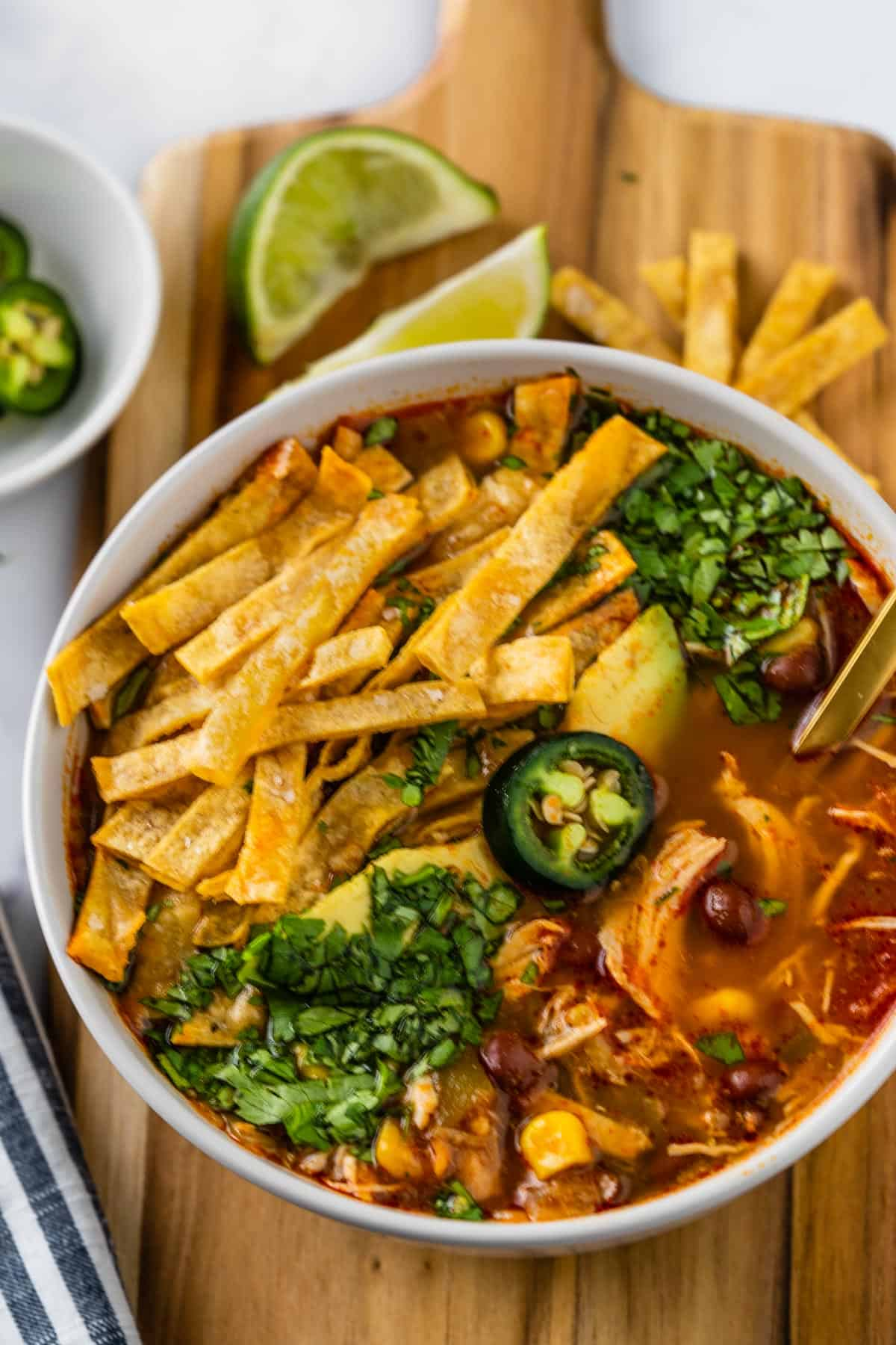 Bowl of chicken tortilla soup on a cutting board with sliced jalapeno peppers, lime wedges and tortilla chips surrounding it