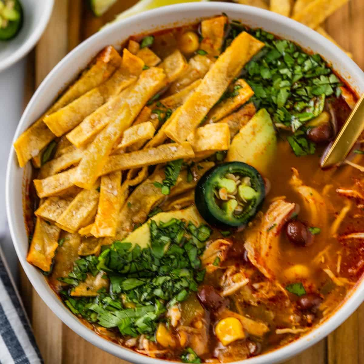 Up close of chicken tortilla soup in a bowl. Chunks of chicken, beans, corn topped with tortilla chips, avocado, jalapeno and cilantro