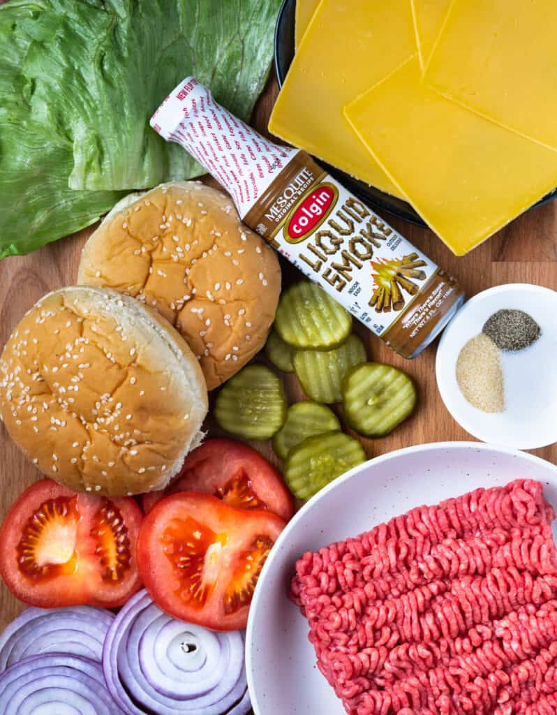 ingredients for burger laid out on a cutting board: lettuce, buns, cheese, seasoning, tomato, onion, pickles, ground beef, and liquid smoke.
