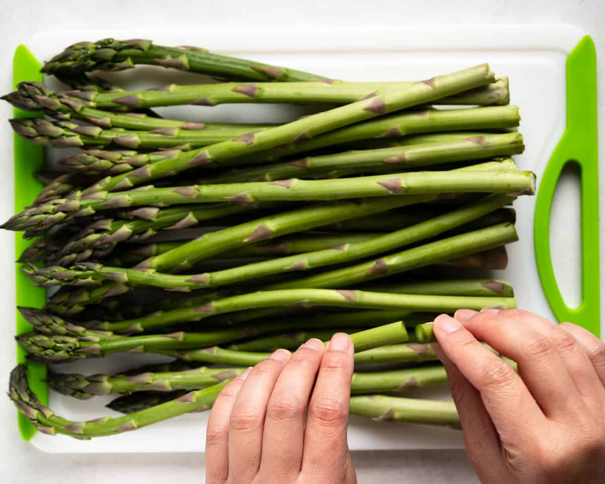 Hands showing how to snap off an asparagus end