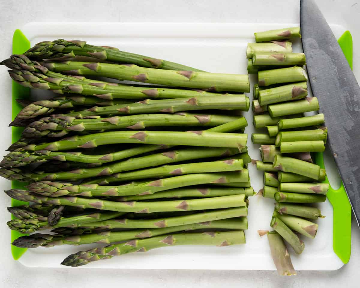 Asparagus on a cutting board with the ends cut off by a knife