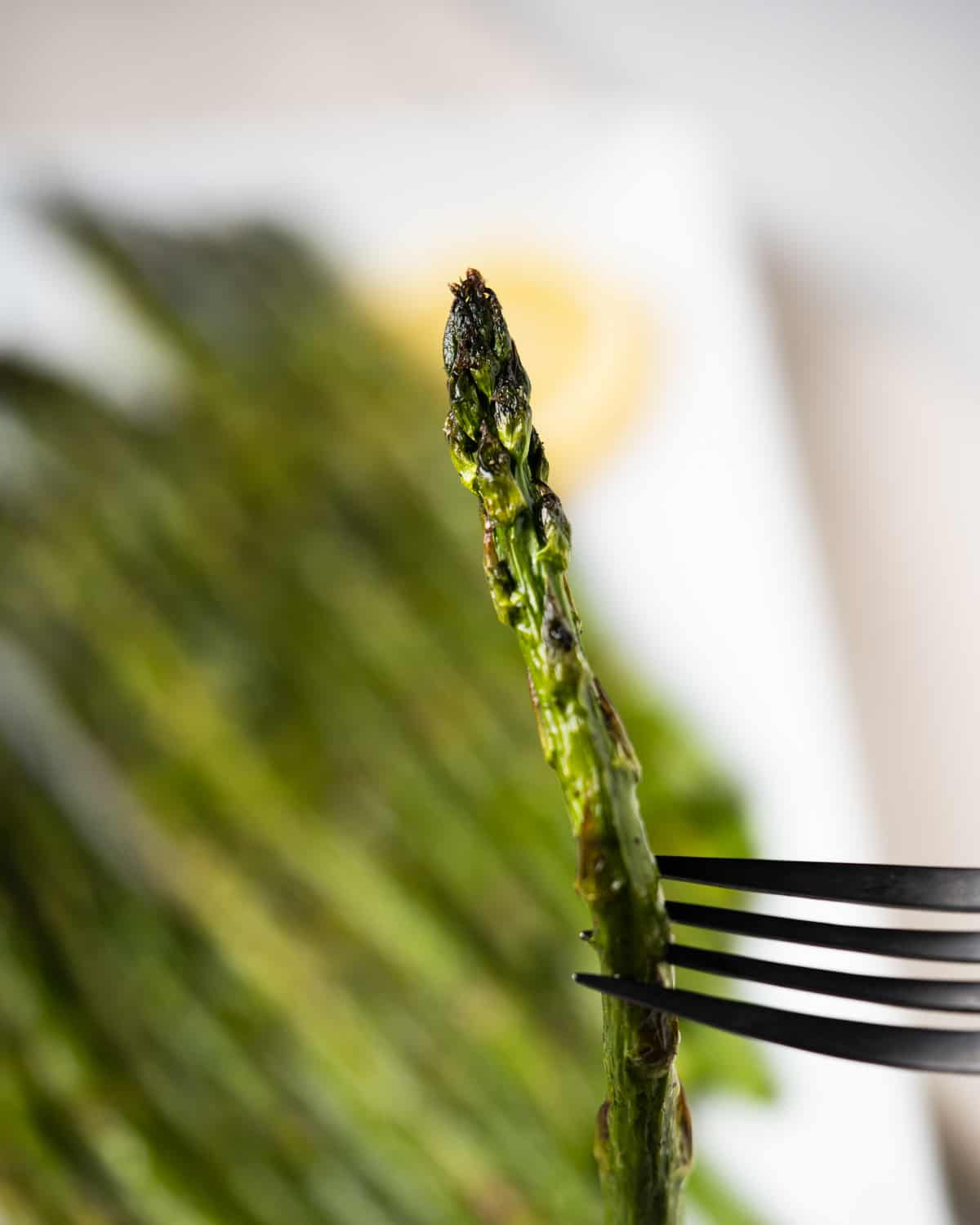 Up close of fork holding up an asparagus cooked in the air fryer