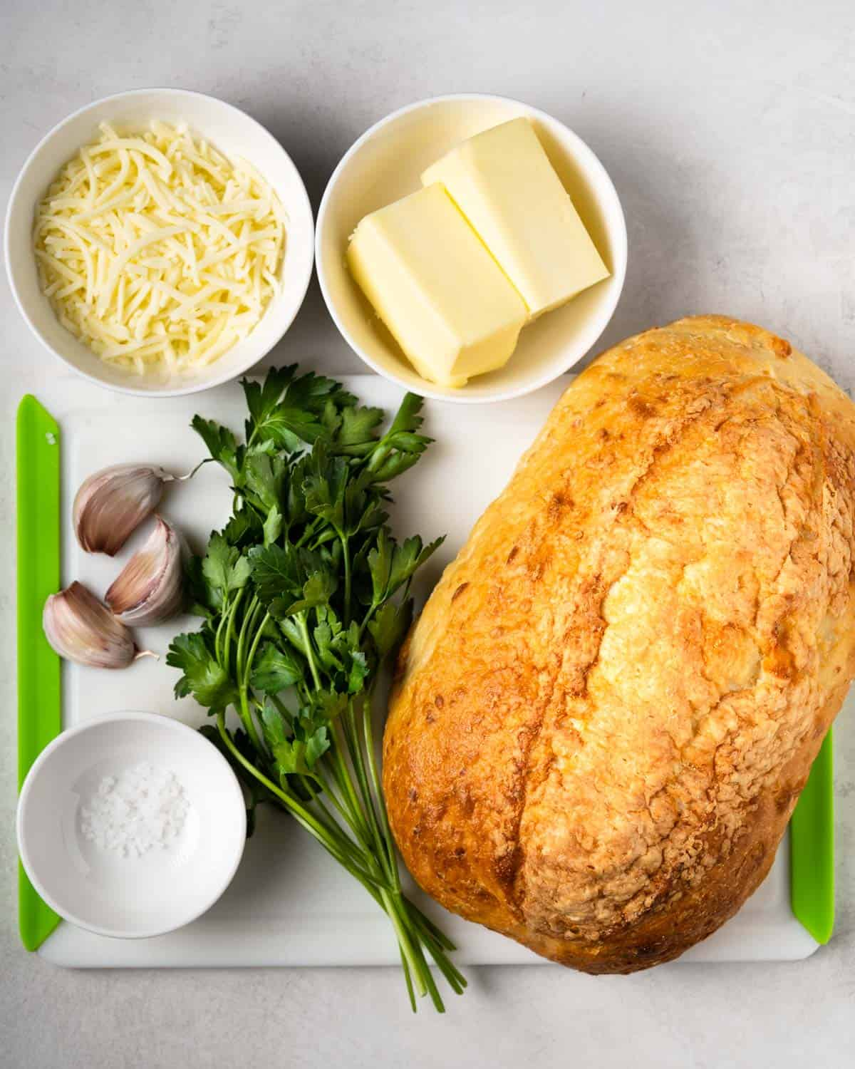 all the ingredients needed to make this recipe: cheese, butter, garlic, parsley, bread, salt