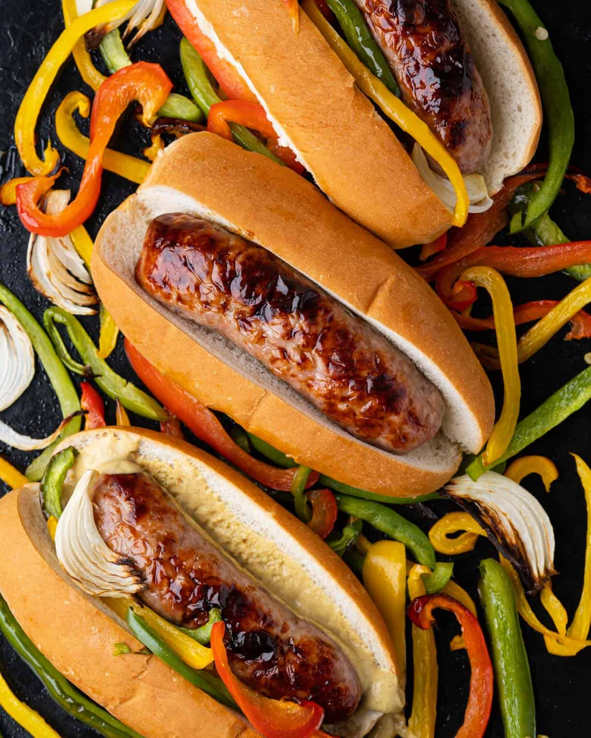 Brats inside buns with grilled onions and peppers