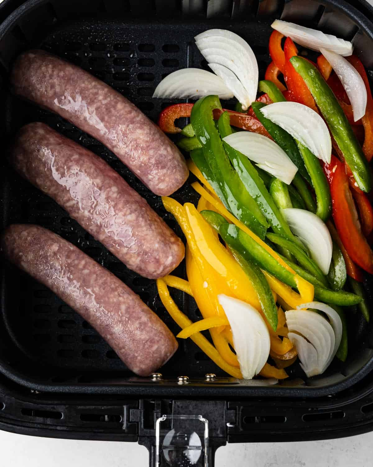 Uncooked brats, onions and peppers inside the air fryer