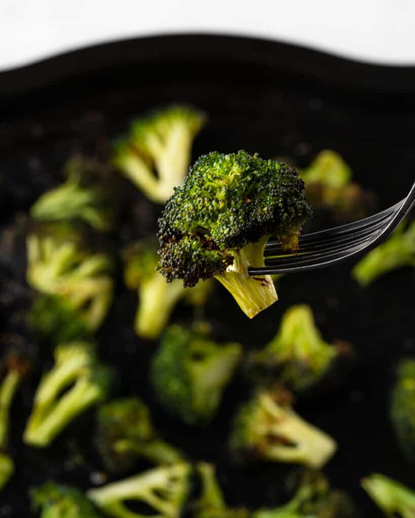 fork holding an air fried broccoli