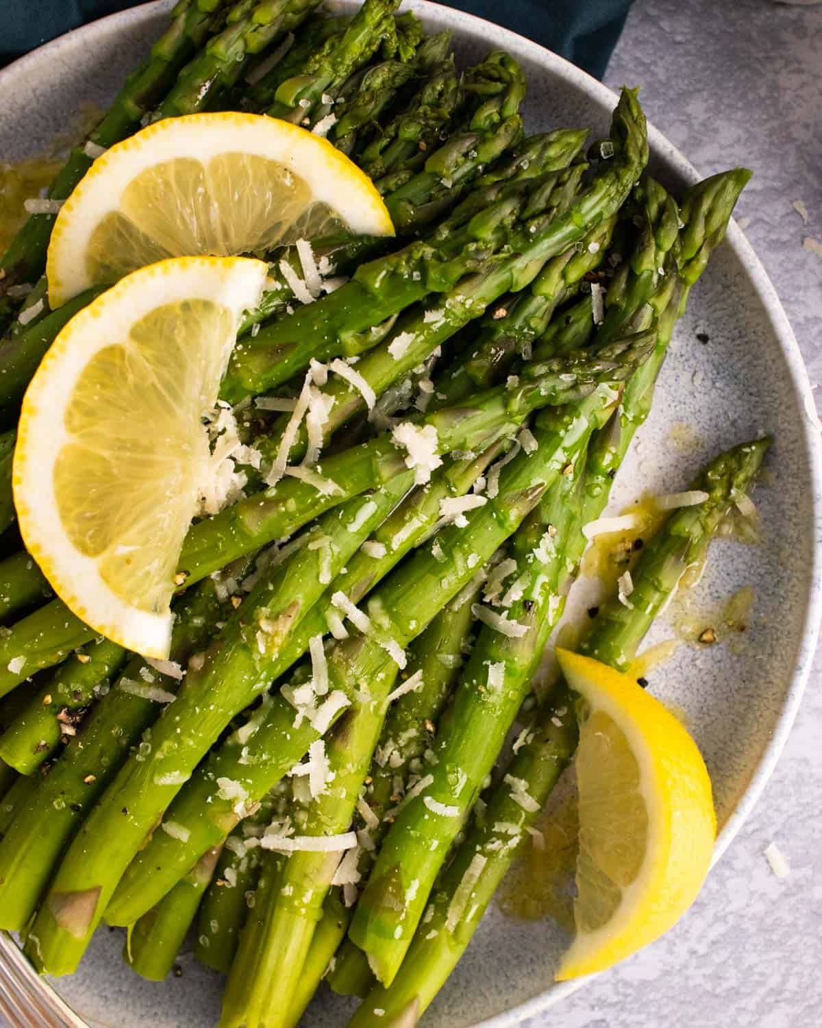 Instant Pot steamed asparagus on a plate with lemon wedges and Parmesan.