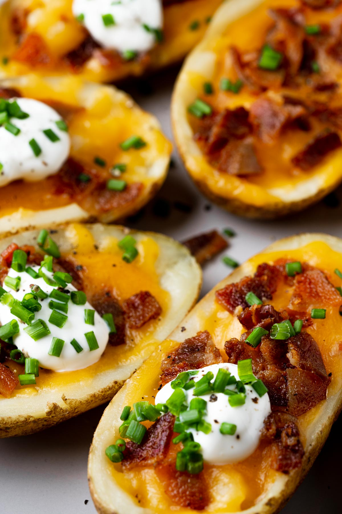 plate of air fryer potato skins with cheese, bacon and chives